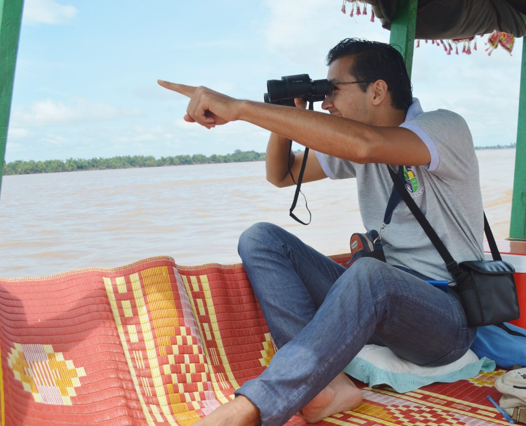 one person sitting and pointing at irrawaddy mekong dolphin and watching with binoculars in kratie crdt tours dolphin boat tour 2018